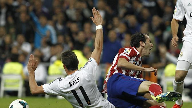 Real Madrid's Gareth Bale, left, tackles Atletico de Madrid's Diego Godin from Uruguay during a Spanish La Liga soccer match at the Santiago Bernabeu stadium in Madrid, Spain, Saturday, Sept. 28, 2013