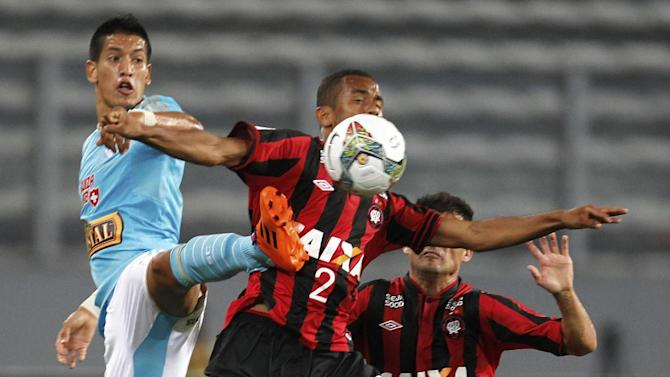 Sueliton of Brazil's Atletico Paranaense, center, fights for the ball with Alexis Cossio of Peru's Sporting Cristal, left, during a Copa Libertadores soccer match in Lima, Peru, Wednesday, Jan. 29, 2014. Pictured at right is Paulo Dias of Brazil's Atletico Paranaense