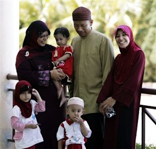 Ishak Md Nor, 40, is surrounded by his wives, Aishah Abdul Ghafar, left, 40, and Afiratul Abidah Mohd Hanan, 25, who are members of the newly launched Obedient Wives Club in Malaysia. (AP Photo)