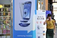 """A woman walks past a signboard for the Samsung Galaxy S3 at a mobile phone shop in Seoul. South Korea's Samsung Electronics vowed on Tuesday to take """"all necessary measures"""" to keep its products on US store shelves, in response to Apple's request for a ban on sales of some smartphones"""