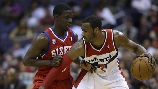 """In this April 12, 2013 file photo, Washington Wizards point guard John Wall, right, is guarded by Philadelphia 76ers point guard Jrue Holiday during the second half of an NBA basketball game in Washington. The aim is pretty clear for Wall and the rest of the Washington Wizards: get to the postseason. Team president Ernie Grunfeld says so. As does coach Randy Wittman. Speaking at a joint news conference Wednesday, Grunfeld says, """"Our initial goal is to be a playoff contender and, ultimately, by the end of the year, make the playoffs."""" Wittman adds, """"We want to make the playoffs. ... And there's no reason why we can't.""""  Washington went 29-53 last season, missing out on the postseason for the fifth consecutive year"""