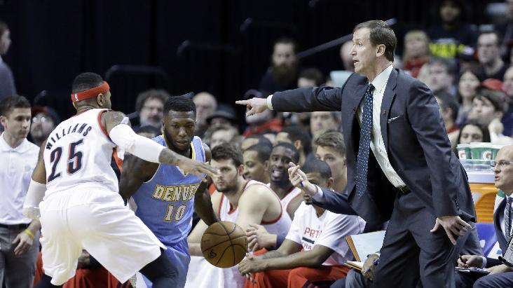 Portland Trail Blazers coach Terry Stotts, right, calls the shots from the bench as Trail Blazers guard Mo Williams, left, guards Denver Nuggets guard Nate Robinson during the second half of an NBA basketball game in Portland, Ore., Thursday, Jan. 23, 2014.  Portland won 110-105