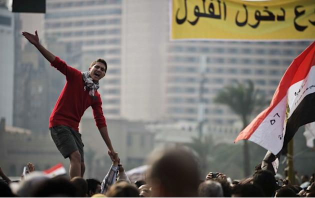 An Egyptian protester shouts political slogans against President Mohamed Morsi's decree granting himself broad powers as others wave their national flag during a demonstration in Cairo's Tahrir Square