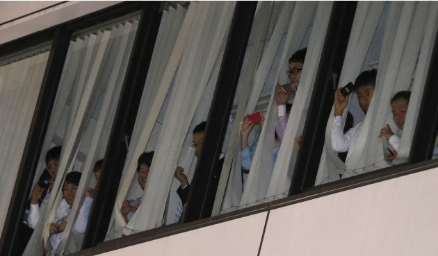 Office workers try to catch a glimpse of U.S. President Barack Obama as Obama and Japanese Prime Minister Shinzo Abe have dinner in Ginza district in Tokyo, Wednesday, April 23, 2014. Opening a four-c