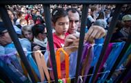 People attach colourful ribbons with the names of Jewish children on the fence of a former Jewish orphanage during ceremonies in Warsaw marking the 70th anniversary of the start of Nazi Germany's mass deportation of Jews from the Warsaw Ghetto to the death camp of Treblinka