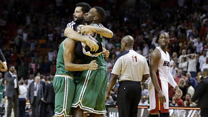 Boston Celtics' Jeff Green, center, is hugged by his teammates after he shot a game-winning three-point basket during the second half of an NBA basketball game against the Miami Heat, Saturday, Nov. 9, 2013, in Miami. The Celtics won 111-110. At right is Miami Heat's Dwyane Wade