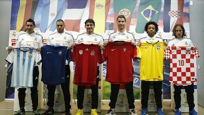 Real Madrid's Cristiano Ronaldo from Portugal centre right, Iker Casillas, centre left, Angel Di Maria from Argentina, left, Karim Benzema from France, second left, Marcelo from Brazil, second right, and Luka  Modric from Croatia, right, pose with their national t-shirts during a press conference on the 2014 soccer World Cup in Madrid, Spain, Sunday, Dec. 8, 2013