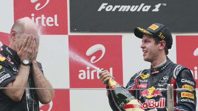 Red Bull driver Sebastian Vettel of Germany, right, sprays champaign to Red Bull's chief technical officer Adrian Newey during the award ceremony of the Indian Formula One Grand Prix at the Buddh International Circuit in Noida, 38 kilometers (24 miles) from New Delhi, India Sunday, Oct. 30, 2011. (AP Photo/Eugene Hoshiko)