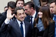 France's incumbent president and Union for a Popular Movement (UMP) candidate for the presidential election Nicolas Sarkozy (left) arrives with his wife Carla Bruni Sarkozy at a polling station on May 6, in Paris