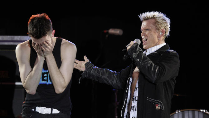 Billy Idol, right, is joined on stage by Michael Henrichsen, left, as Idol performs Friday, Oct. 26, 2012, in Seattle. Idol came to play in Seattle after Henrichsen launched a two-year grass-roots campaign to convince the rock star to play for his birthday party. (AP Photo/Ted S. Warren)
