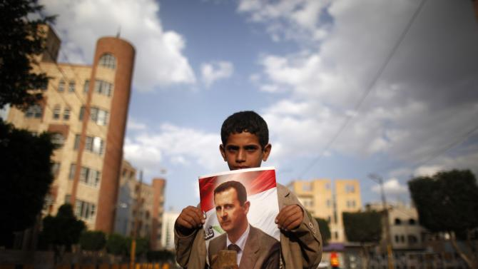 A boy holds a poster of Syria's President during a demonstration against potential strikes on the Syrian government, in Sanaa