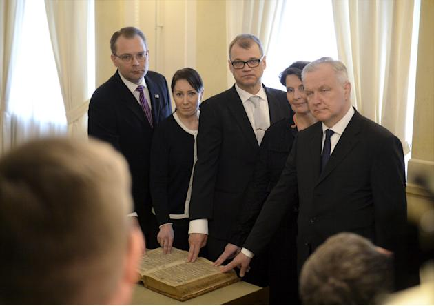 Taking the vow of office, Finland government ministers from left: Minister of Defence Jussi Niinisto, Minister of Social Affairs and Health Hanna Mantyla, Prime Minister Juha Sipila, Minister of Trans