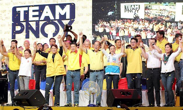 President Benigno Aquino III, also Liberal Party (LP) Chairman, lifts the hands of the LP bets for the upcoming 2013 midterm elections, during the LP proclamation rally held at Plaza Miranda infront of the Quiapo Church in Manila, 12 February 2013. Today is the start of the 90-day campaign period given to candidates running for elected positions in the May 13, 2013 elections. (Czeasar Dancel/NPPA Images)