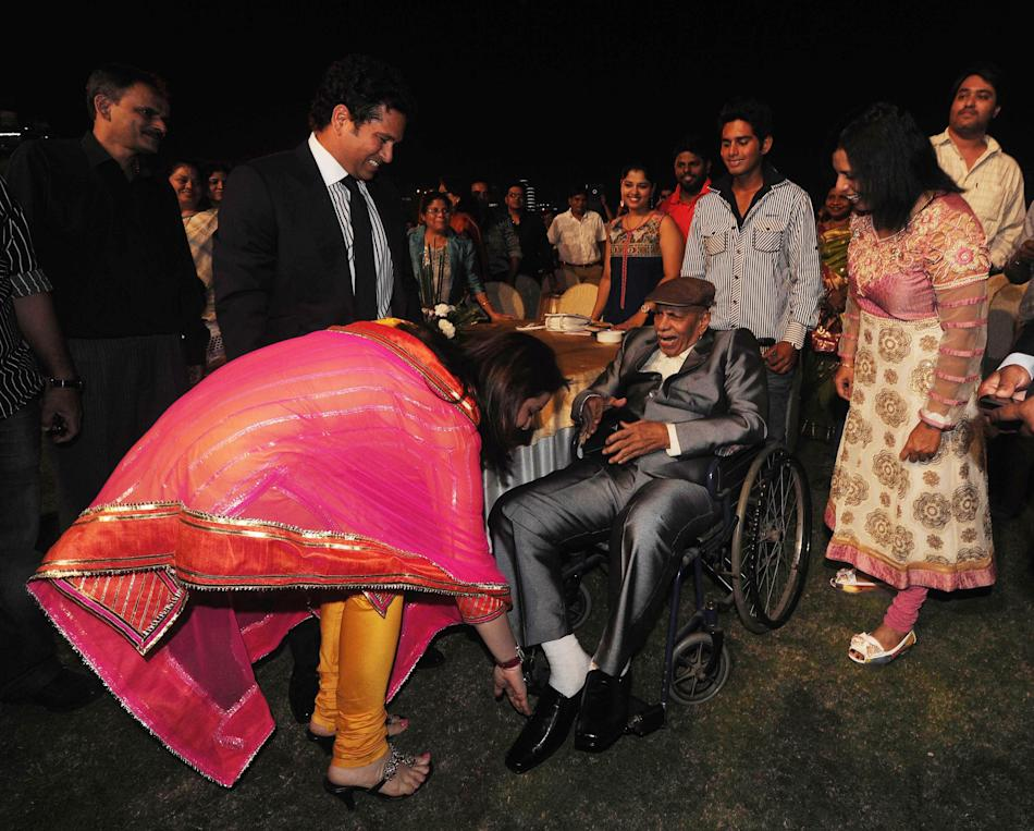 Cricket legend Sachin Tendulkar with his wife Anjali who is touching feet of Sachin's coach Ramakant Achrekar as a gesture of respect during inauguration of Sharad Pawar Indoor Cricket Academy and