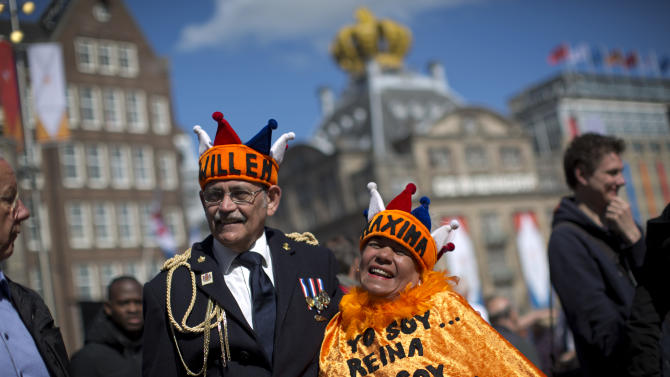 Couple Reina Reyes and Asdrubal Medina  from Venezuela pose for a photograph outside the Royal Palace in downtown Amsterdam, in downtown Amsterdam, Netherlands Monday, April 29, 2013. Queen Beatrix has announced she will relinquish the crown on April 30, 2013, after 33 years of reign, leaving the monarchy to her son Crown Prince Willem-Alexander. (AP Photo/Emilio Morenatti)
