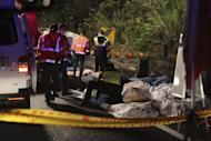 Bodies are covered as emergency services attend the scene of a crash where a bus collided with a car on a highway in Taipei, Taiwan, Monday, Feb. 13, 2017. A tour bus has flipped over on a highway near Taiwan's capital, killing over 30 people and trapping many others, officials said. (AP Photo)
