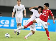 In this file photo, Real Madrid's Marcelo Vieira da Silva Jr. (C) is seen fighting for the ball with Guangzhou Evergrande's Wu Pingfeng during their pre-season friendly at the Tianhe Stadium in Guanzhou, southern China, in 2011. Real are to open a football academy in southern China next year in a tie-up with Super League leaders Guangzhou Evergrande, the Chinese club's owner said on its website