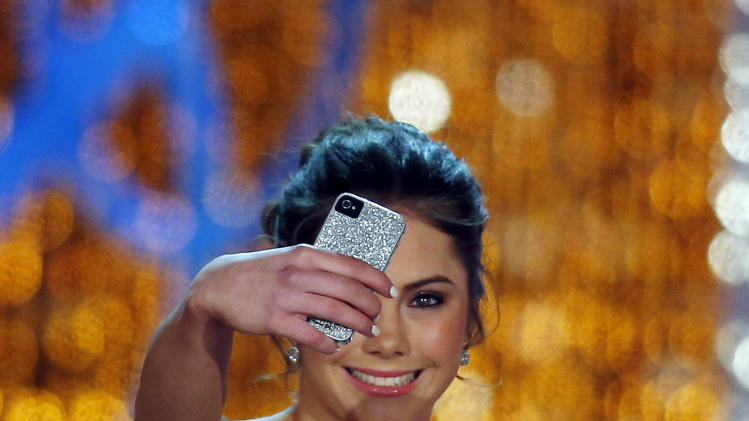 Miss America judge McKayla Maroney photographs herself onstage before the pageant on Saturday, Jan. 12, 2013, in Las Vegas. (AP Photo/Isaac Brekken)