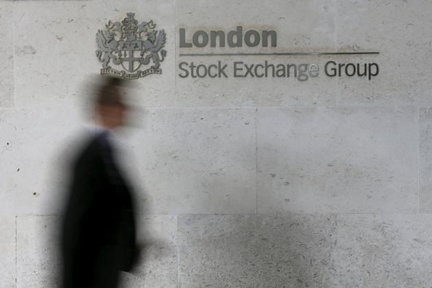 File photo of a man walking past the London Stock Exchange in the City of London