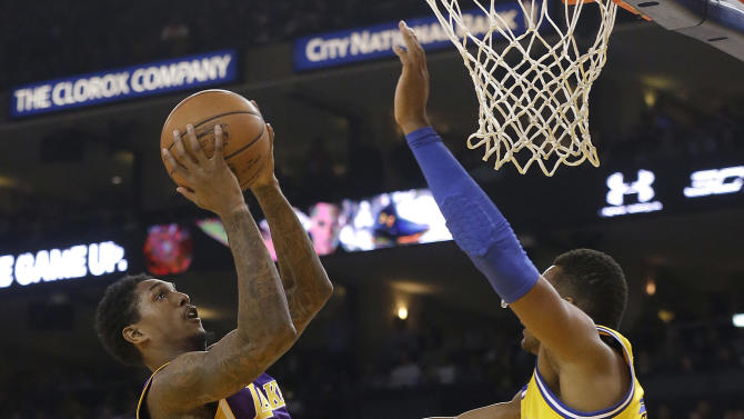 Los Angeles Lakers guard Lou Williams, left, shoots against Golden State Warriors guard Leandro Barbosa during the first half of an NBA basketball game in Oakland, Calif., Tuesday, Nov. 24, 2015. (AP Photo/Jeff Chiu)
