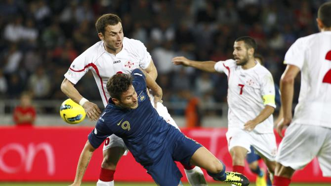 Georgia's Akaki Khubutia fights for the ball with France's Olivier Giroud during their 2014 World Cup qualifying soccer match at the Boris Paichadze National Stadium in Tbilisi
