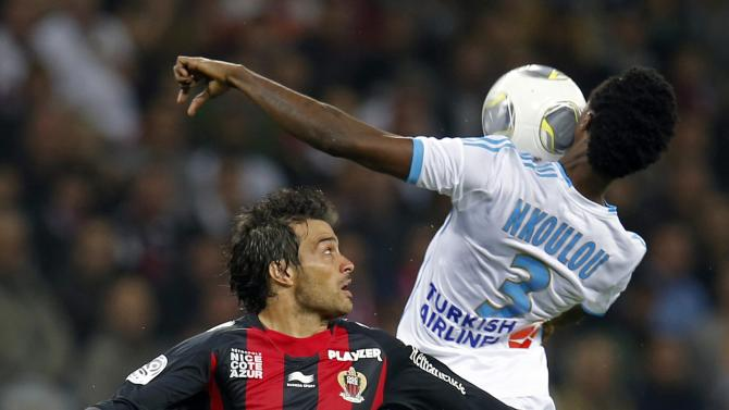 Nice's Dario Cvitanich fights for the ball with Olympique Marseille's Julio Nkoulou during their French Ligue 1 soccer match at Allianz Riviera stadium in Nice