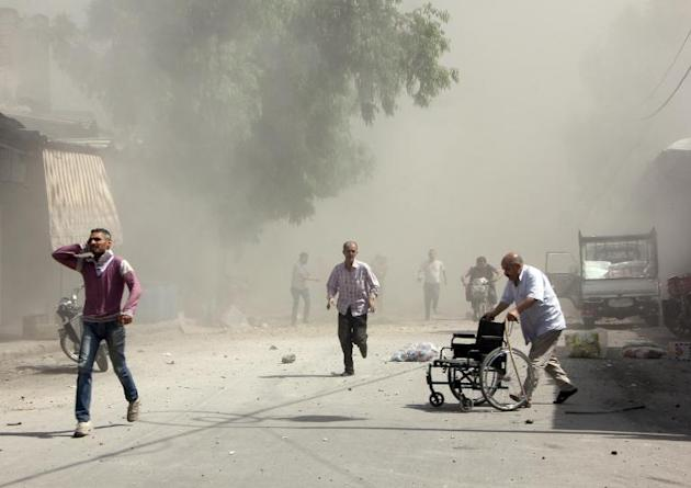 Syrian men react following a reported barrel bomb attack by Syrian government forces that hit an open market in the northern city of Aleppo, on June 2, 2015