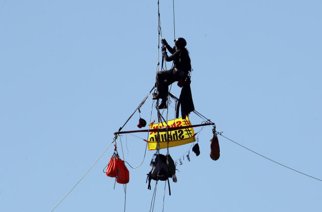 An activist  hangs from the St. Johns Bridge in Portland, Ore., Wednesday, July 29, 2015, to protest the departure of Royal Dutch Shell PLC icebreaker Fennica, which is in Portland for repairs. The ic