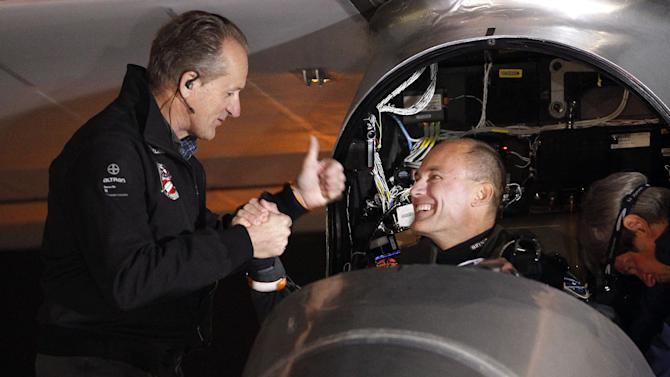 Pilots Bertrand Piccard, right, and André Borschberg, left shake hands before the Solar Impulse plane takes off to embark on a multi-city trip across the United States from Moffett Field NASA Ames Research Center in Mountain View, Calif., Friday, May 3, 2013. Solar Impulse, considered the world's most advanced solar-powered plane, will stop for seven to 10 days at major airports in each city, so the pilots can display and discuss the aircraft with reporters, students, engineers and aviation fans. It plans to reach New York's Kennedy Airport in early July — without using a drop of fuel, its creators said. (AP Photo/Tony Avelar)