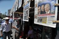 Pedestrians walk past a news-stand in Athens. Conservative leader Antonis Samaras has been sworn in as the prime minister of new Greek coalition, taking up the challenge of trying to revise the terms an unpopular EU-IMF bailout deal