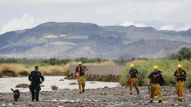 Members of the Henderson police and fire departments head back to their vehicles after conducting a search of the Duck Creek Channel for a missing teenager in Henderson, Nev., on Wednesday, Aug. 22, 2012. According to witnesses, the man was pulled into the heavily flooded wash as intense thunderstorms filled storm channels and sent water into roadways. (AP Photo/Las Vegas Review-Journal, Jason Bean) LOCAL TV OUT; LOCAL INTERNET OUT; LAS VEGAS SUN OUT