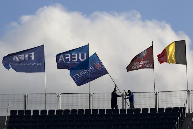 Workers hang UEFA flags ahead of tomorrow's Euro 2016 Group B qualifying soccer match between Israel and Belgium at Teddy Stadium in Jerusalem