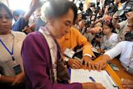 Myanmar opposition leader Aung San Suu Kyi signs the attendance sheet as she arrives at the lower house of parliament to read her parliamentary oath. The Myanmar pro-democracy leader was sworn in as a member of parliament Wednesday, opening a new chapter in the Nobel laureate's near quarter-century struggle against authoritarian rule