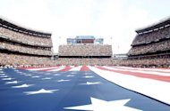 Fans listen to the national anthem as an American flag is spread across the field at Cleveland Browns stadium in 2011. An assistant groundskeeper for the Browns killed himself at the NFL team's practice facility, NFL.com reported Sunday, exacerbating an already traumatic weekend for the sport