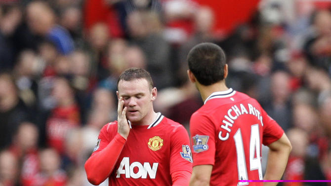 Manchester United's Wayne Rooney, left, reacts after a goal as his team are beaten 6-1 by Manchester City in their English Premier League soccer match at Old Trafford Stadium, Manchester, England, Sunday Oct. 23, 2011. (AP Photo/Jon Super)