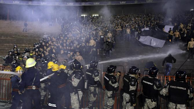 Firemen try to extinguish flames on the stands as members of the Serbian Gendarmerie provide security during a Serbian soccer league fixture between arch rivals Red Star and Partizan Belgrade in Belgrade, Serbia, Saturday, Nov. 2, 2013. Marred with bouts of fan violence and frequent match fixing scandals, Serbian soccer seems to be in deep crisis, resulting with the national team failing to qualify for the 2014 World Cup