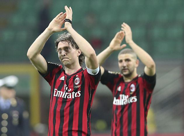 AC Milan midfielder Riccardo Montolivo, left, celebrates with his teammate forward Adel Taarabt, of Morocco, at the end of the Serie A soccer match between AC Milan and Catania at the San Siro stadium