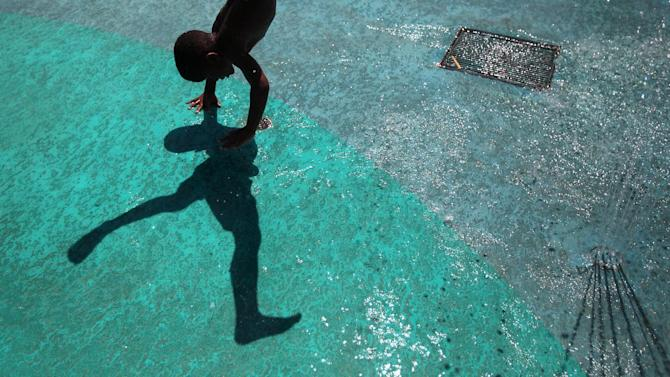 Malik Coleman, 6, plays in the water spray grounds at James Wiley Park near downtown on Friday, June 28, 2013, in Houston. (AP Photo/Houston Chronicle, Mayra Beltran)