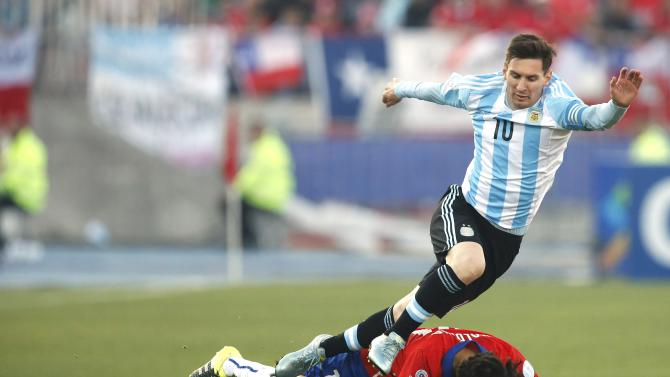 Argentina's Lionel Messi trips on Chile's Jorge Valdivia during their Copa America 2015 final soccer match at the National Stadium in Santiago