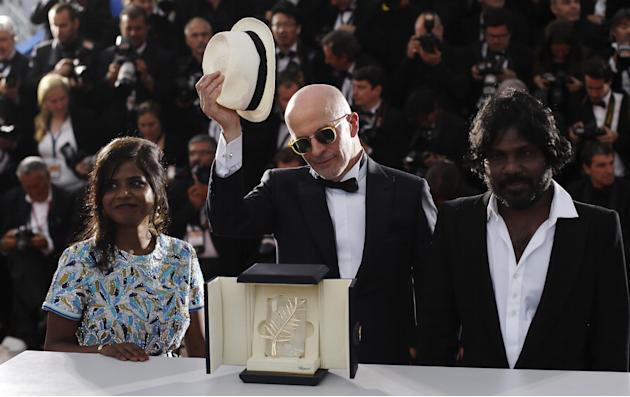 Director Jacques Audiard, center, poses with the Palme d'Or award for the film Dheepan alongside actors Jesuthasan Antonythasan, right, and Kalieaswari Srinivasan, left, during a photo call following