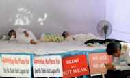 "Air India pilots from the Indian Pilots Guild lie on a dias during a hunger strike in New Delhi. Hundreds of state-run Air India pilots agreed Tuesday to call off their nearly two-month strike after the airline management said it would consider their grievances ""sympathetically"""