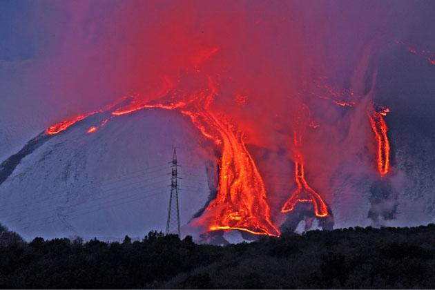 Red hot lava flows down Italian volcano Mount Etna as it erupts. The volcano erupted three times over 36 hours (Photo by Olycom SPA / Rex Features)