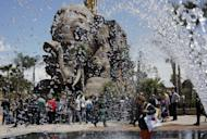 "In this July 10, 2014 photo, journalists gather in front of a gigantic elephant statue part of the adventurous family ride ""Erawan - The lost Temple"", a 54 meter drop tower, as they visit the Cinecitta World theme park in the outskirts of Rome. Cinecitta World is a theme park, inspired to the Cinecitta film studios in Rome. Academy Award winning art director Dante Ferretti designed the attractions at the 500 million Euros (680 million US dollars) park that opened to the public on July 24. (AP Photo/Domenico Stinellis)"