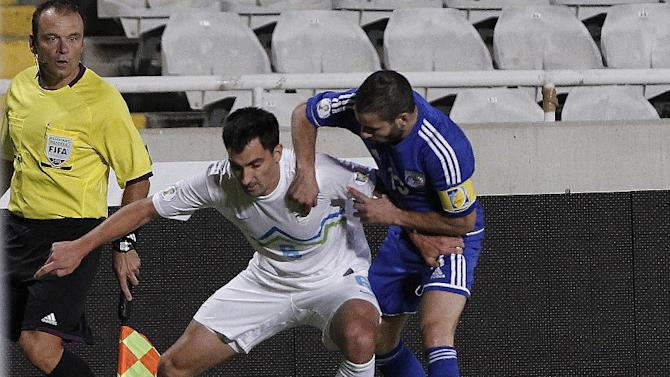 Cyprus' Konstantinos Mkrides, right, fights for the ball with Slovenia's Branko Ilic during their World Cup group E qualifying soccer match at GSP stadium in Nicosia, Cyprus, Tuesday, Sept. 10, 2013