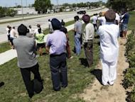 Bystanders look on as SWAT officers surround the Sikh Temple of Wisconsin where a gunman attacked worshippers on Sunday killing at least six people before he was himself shot dead by police