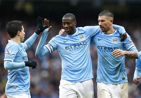 Manchester City's Toure celebrates with team mates Nasri and Kolarov after scoring a third goal against Fulham during their English Premier League soccer match at the Etihad stadium in Manchester