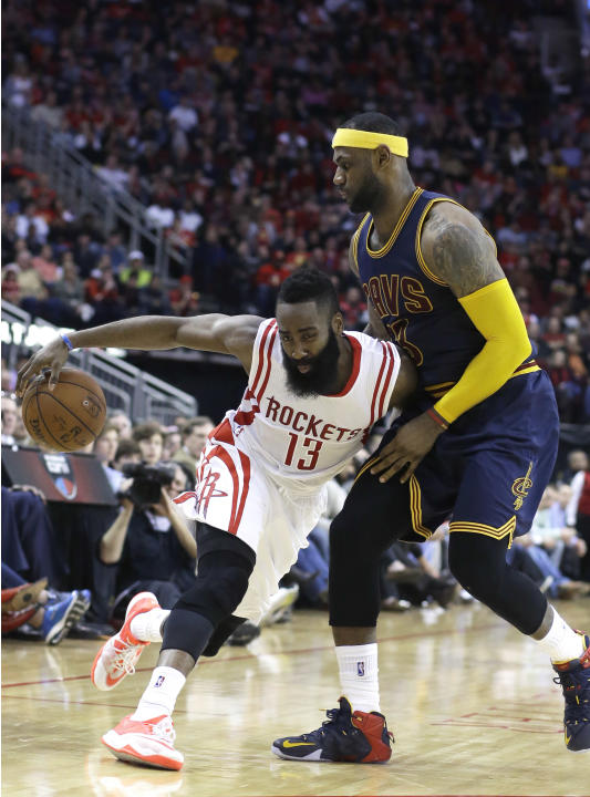 Houston Rockets' James Harden (13) pushes against Cleveland Cavaliers' LeBron James (23) in the second half of an NBA basketball game Sunday, March 1, 2015, in Houston. The Rockets won 105-103