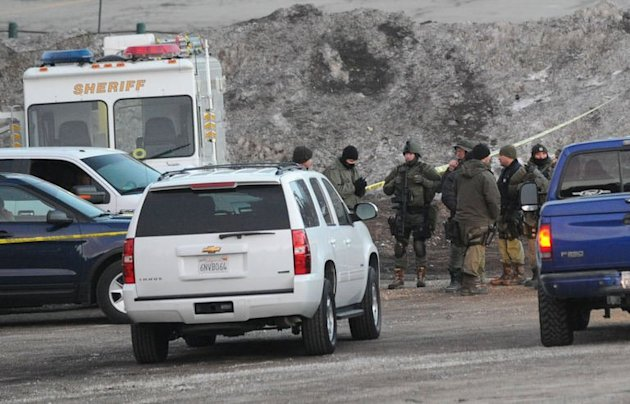 Sherriff's deputies carrying assault weapons are seen at a police commander center in Big Bear, California during the manhunt for alleged cop-killer fugitive Christopher Dorner, February 7, 2013. Police vowed to keep searching as night fell over a California ski resort where his burnt-out truck was found