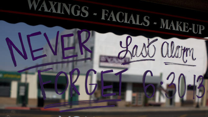 A message written on the window of a local beauty shop, Wednesday, July 3, 2013, in Prescott, Ariz., is addressed to the 19 Granite Mountain Hotshot firefighters who died when an out-of-control blaze overtook them near Yarnell, Ariz. on Sunday. From the picturesque town square to famous Whiskey Row, life goes on in Prescott, but so, too, does the mourning for their lost heroes, some of them native sons. (AP Photo/Julie Jacobson)