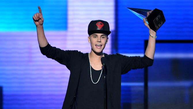 "FILE - In this Nov. 18, 2012 file photo, Justin Bieber accepts the award for favorite album - pop/rock for ""Believe"" at the 40th Anniversary American Music Awards, in Los Angeles. A Los Angeles appellate panel wrote in a preliminary statement filed Monday, Jan. 28, 2013, that a 2010 California anti-paparazzi statute is constitutional. The law was used to charge a photographer for chasing Bieber last year, but a judge dismissed the anti-paparazzi counts in November 2012 because he said the law is overly broad and unconstitutional. (Photo by John Shearer/Invision/AP, File)"